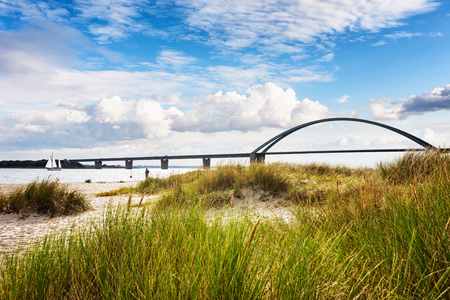 Photo for Fehmarn sound bridge. Late summer landscape with beach, dune grass and cloudy sky. Vacation background. Baltic sea coast, Germany, travel destination - Royalty Free Image