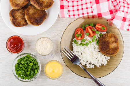 Foto de Fried cutlets with rice, tomatoes, green onion in brown plate, bowls with horseradish, mayonnaise, ketchup and fork on wooden table. Top view - Imagen libre de derechos