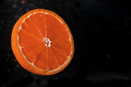 Photo for Orange slice on black background submerged in water with bubbles - Royalty Free Image