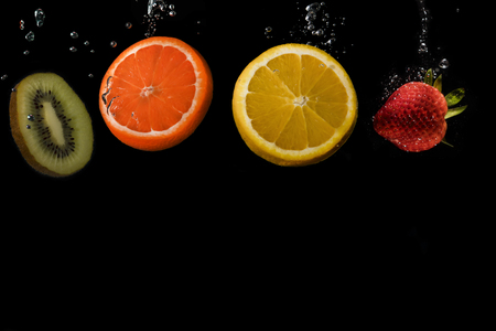Photo for Four slices of fruit lined up, with space below to add text: Kiwi, Orange, Lemon and strawberry. Black background. - Royalty Free Image