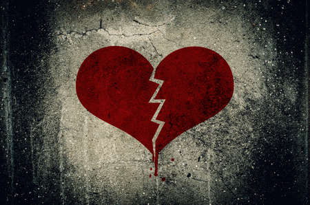 Foto de Heart broken painted on grunge cement wall background - love concept - Imagen libre de derechos