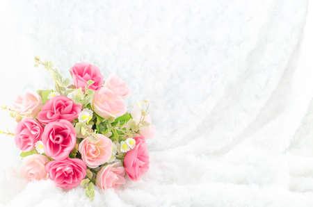 Photo pour Pastel Coloured Artificial Pink Rose Wedding Bridal Bouquet on white fur background with soft vintage tone - image libre de droit