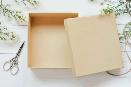 Photo pour Opened brown gift box on wooden background with white daisy flower and vintage tone - image libre de droit