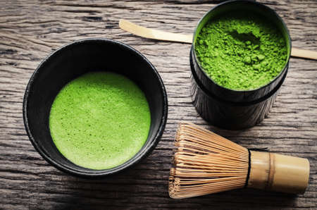 Photo pour Japanese matcha green tea and matcha green tea powder at homemade clay bowl with bamboo whisk on wooden table with vignette tone - image libre de droit