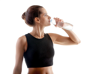Sporty yoga girl on white background drinking water after practice
