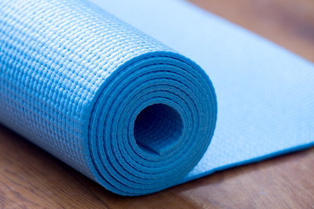 Photo for Close up of rolled blue yoga, pilates mat on the floor. Healthy life, keep fit concepts - Royalty Free Image