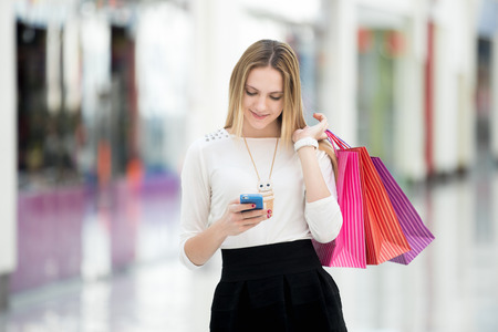 Photo for Happy teenage girl holding bags with purchases, smiling while looking at phone in shopping center. Received good news, reading message, texting, dialing number, using app on smartphone - Royalty Free Image