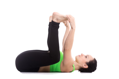 Foto de Sporty girl on white background lying in yoga Happy Baby pose, Ananda Balasana, relaxing, aligning back, stretching spine, legs, relieving stress and fatigue - Imagen libre de derechos
