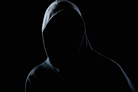 Photo pour Young man in black hooded sweatshirt invisible in the night darkness, dimly lit, concepts of danger, crime, terror - image libre de droit