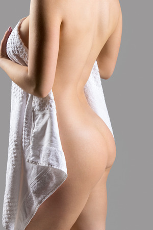 Photo pour Close-up of unrecognizable sexy beautiful nude young woman hiding behind towel, back view, drying off after shower, weight loss, health and skincare concepts - image libre de droit
