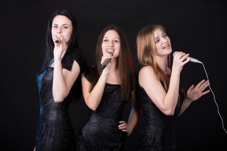 Photo for Group of three emotional beautiful young female singers with microphones singing, girls band concert - Royalty Free Image