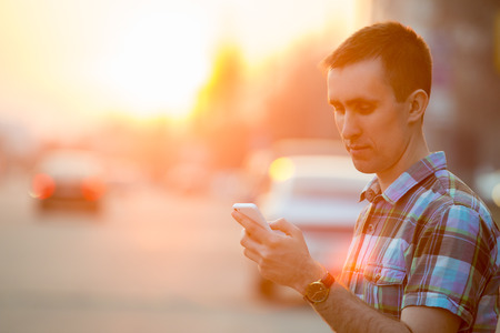 Foto de Young man holding mobile phone, using smartphone app, scrolling, looking at screen, standing on sunny street with transport vehicles on the background - Imagen libre de derechos