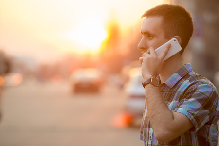 Foto de Young man holding mobile phone, using smartphone, making a call, talking on the phone, standing on sunny street with transport traffic on the background - Imagen libre de derechos