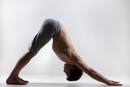 Foto de Profile of muscular handsome young man working out, standing in yoga downward facing dog pose, adho mukha svanasana, asana from Surya Namaskar sequence, Sun Salutation complex, low key shot - Imagen libre de derechos