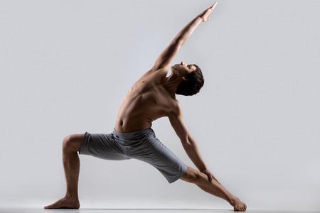 Foto de Sporty muscular young man working out, yoga, pilates, fitness training, high lunge exercise, Reverse Warrior Pose, Crescent variation, Viparita Virabhadrasana, gray background, low key shot - Imagen libre de derechos