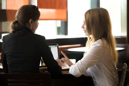 Photo pour Two young caucasian office women meeting, discussing business, sitting at the table, beside laptop, rear view - image libre de droit