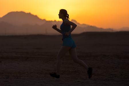 Silhouette of young sporty woman doing running training in colorful picturesque mountainous landscape, mountains and sky on horizon lit by sun
