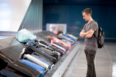 Photo for Young handsome man passenger in his 20s with carry-on backpack waiting at conveyor belt to pick his luggage in arrivals lounge of airport terminal building - Royalty Free Image