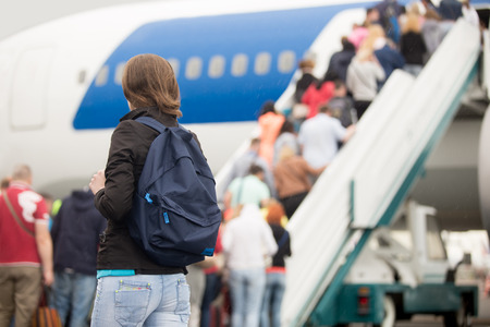Photo pour Young woman passenger in 20s travelling with backpack, boarding airplane, people climbing ramp on background, rear view - image libre de droit