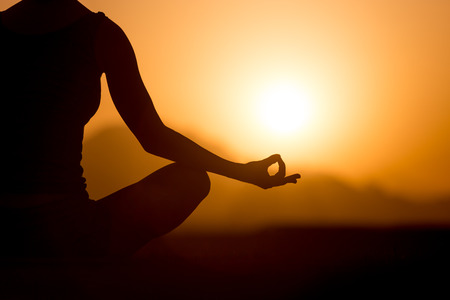 Photo for Silhouette of young woman sitting cross-legged with fingers in yogic Jnana mudra. Relaxation, meditation in beautiful mountainous landscape at sunset or sunrise, close up, copy space - Royalty Free Image