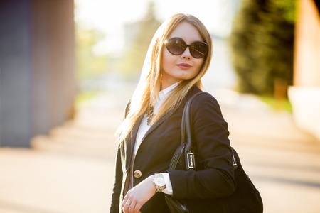 Photo pour Portrait of young beautiful blond woman wearing sunglasses and fashionable black suit on sunny street - image libre de droit