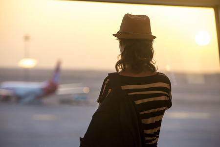 Photo pour Young woman in straw hat and summer dress with backpack waiting for flight in modern airport terminal building, watching airplanes in window on sunrise or sunset, back view - image libre de droit