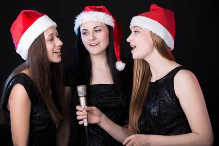 Group of three positive, happy smiling beautiful young female singers singing in cute red santa claus hats, black background