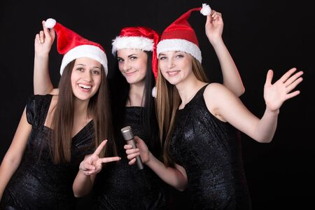 Group of three positive, happy smiling beautiful girls singers posing in cute red santa claus hats with microphone, black background