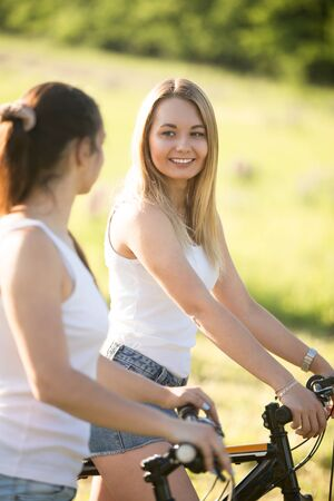 Two young beautiful cheerful women girlfriends wearing jeans shorts on bicycles in park on sunny summer day, having good time, talking to each other, focus on smiling blond woman