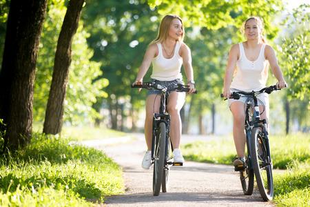 Two happy smiling young women girlfriends wearing jeans shorts enjoy riding bicycles on street on sunny summer day, having conversation