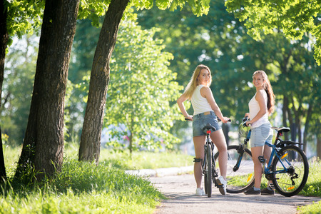 Portrait of two young beautiful cheerful women girlfriends wearing jeans shorts sitting on bikes on sidewalk in park on sunny summer day, looking back with smile