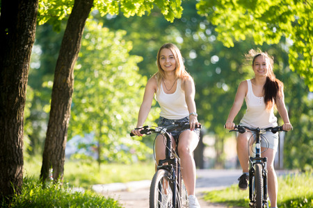 Portrait of two young beautiful cheerful women girlfriends wearing jeans shorts biking on street sidewalk on sunny summer day, having good time, happy smiling