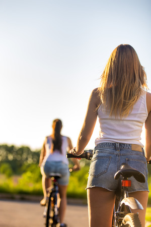 Back view of two sporty beautiful young women on bikes wearing casual white tank tops and jeans shorts on park road on bright sunny summer day