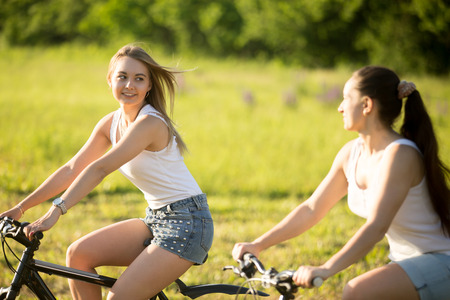Two cute young happy smiling beautiful women girlfriends wearing jeans shorts riding bikes in park in bright sunlight on summer day, chatting together