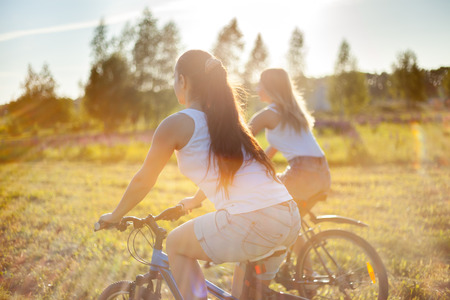 Two young beautiful women girlfriends wearing jeans shorts cycling in park on sunny summer day, lens flare, back view