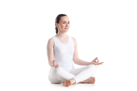 Photo pour Sporty beautiful young woman practicing yoga, Sitting in Easy (Decent, Pleasant Pose), Sukhasana, asana for meditation, pranayama, breathing, studio full length isolated shot, three-quarters view - image libre de droit