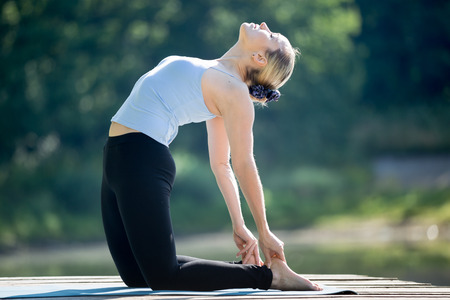 Foto de Beautiful sporty fit blond young woman in blue tank top sportswear working out outdoors in park on summer day, doing ushtrasana, Camel Posture, full length - Imagen libre de derechos