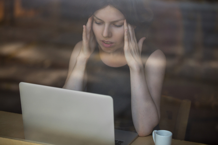 Foto de Young woman sitting in cafe in front of laptop, looking at screen with frustrated expression, holding her head in hands, having headache, low or high arterial blood pressure, stress - Imagen libre de derechos