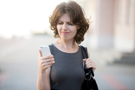 Photo pour Portrait of stressed office young woman holding cellphone in hands on the city street in summer, looking at screen with cross face expression, mad at stressful texts and calls - image libre de droit