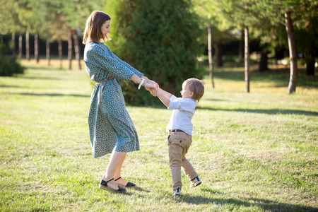 Photo pour Portrait of happy young mom and her adorable little son playing and dancing together in park in summertime, smiling mother and kid holding hands, spinning, having fun together, full length - image libre de droit