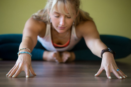 Foto de Sporty beautiful blond young woman in sportswear working out indoors, doing Butterfly Pose with closed eyes, sitting in Purna Titli or Baddha Konasana Posture, full length, close-up, focus on hands - Imagen libre de derechos