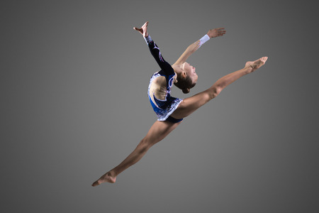 Photo pour Beautiful cool young fit gymnast woman in blue sportswear dress working out, performing art gymnastics element, jumping, doing split leap in the air, dancing, full length, studio, dark background - image libre de droit