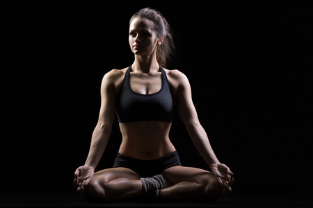 Photo pour Beautiful serene cool young fit woman in sportswear practicing yoga, sitting in Sukhasana, Easy Posture, asana for meditation, pranayama, full length, front view, studio image, black background - image libre de droit