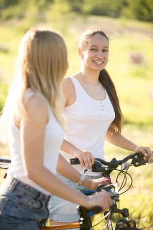 Two young beautiful cheerful women girlfriends wearing jeans shorts on bicycles in park on sunny summer day, having good time, talking to each other