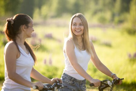 Two cheerful beautiful teenage girls wearing jeans shorts on bicycles in park on sunny summer day, having good time, laughing and chatting, focus on blond young woman