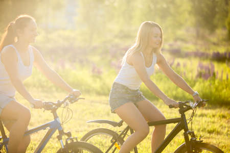 Two cute young happy smiling beautiful women girlfriends wearing jeans shorts riding bikes in park in bright sunlight on summer day