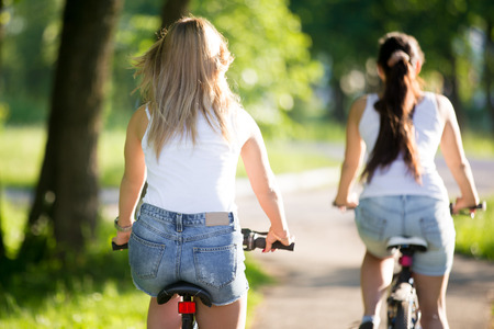 Two young beautiful women girlfriends wearing jeans shorts biking on sidewalk on the street on sunny summer day, back view