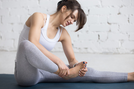 Photo pour Beautiful young woman feeling pain in her foot during sport workout indoors, close-up - image libre de droit