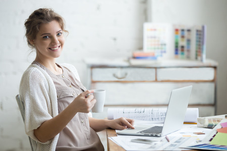 Photo pour Portrait of beautiful happy smiling young designer woman sitting at home office desk with cup of coffee, posing, looking at camera. Attractive cheerful model using computer. Indoors - image libre de droit