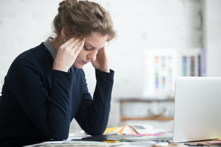 Photo pour Portrait of young stressed woman sitting at home office desk in front of laptop, touching head with frustrated facial expression, having headache, overworked or depressed - image libre de droit